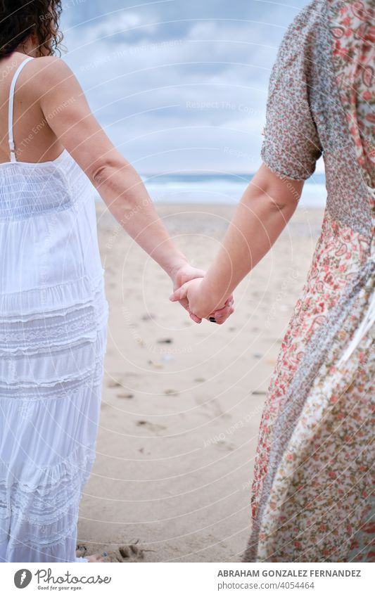 Two girls holding each other hands. Ladies couple on the beach gay lesbian women love girlfriend two together dating dress female ocean pier sexy skin summer