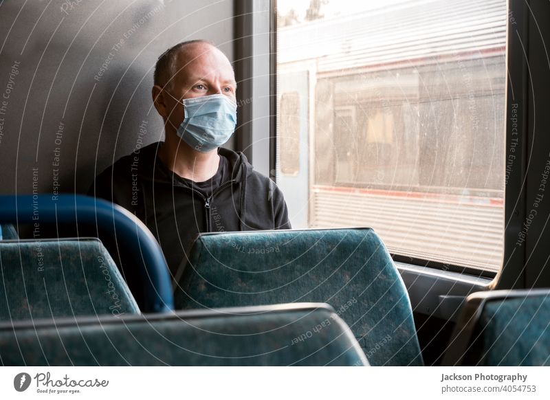 A man wearing surgical mask looking through the window in a train pandemic serious sad copy space public transport covid19 male caucasian corona virus lockdown