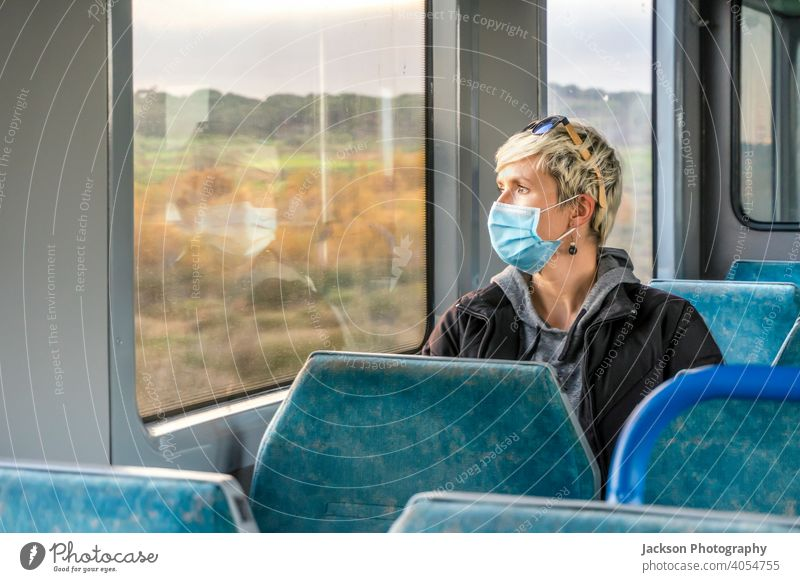 Woman wearing surgical mask looking through the window in a train pandemic woman serious sad copy space public transport covid19 caucasian corona virus lockdown