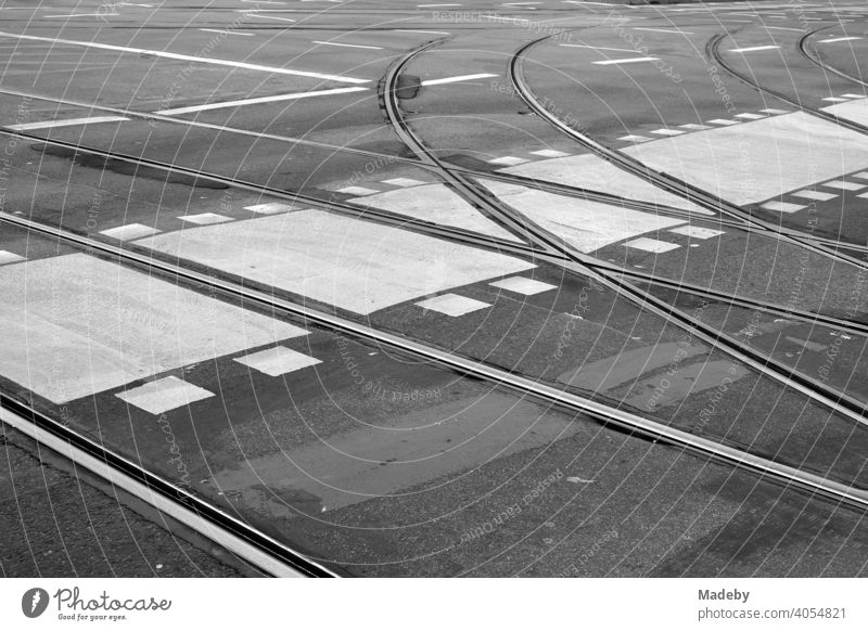 Branching tram tracks with bike lane, pedestrian crossing and other road markings on grey asphalt in the city centre of Frankfurt am Main in Hesse, photographed in classic black and white