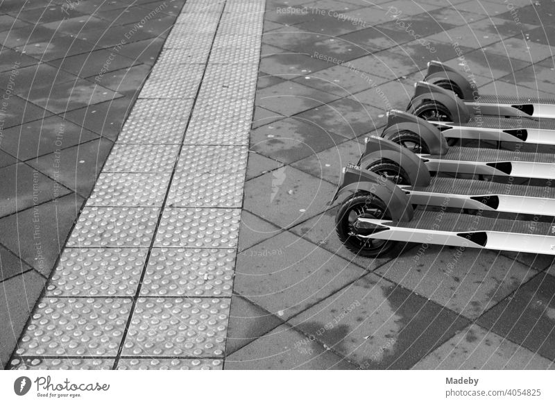 E-scooters lined up for rent next to a tactile guidance system for the visually impaired on grey pavement in the city centre of Frankfurt am Main in Hesse, photographed in neo-realistic black and white