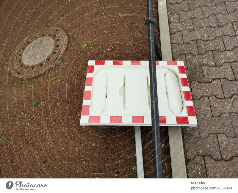Frame of a traffic mirror in red and white without mirror as still life with manhole cover at the roadside in the district Bockenheim in Frankfurt am Main in Hesse