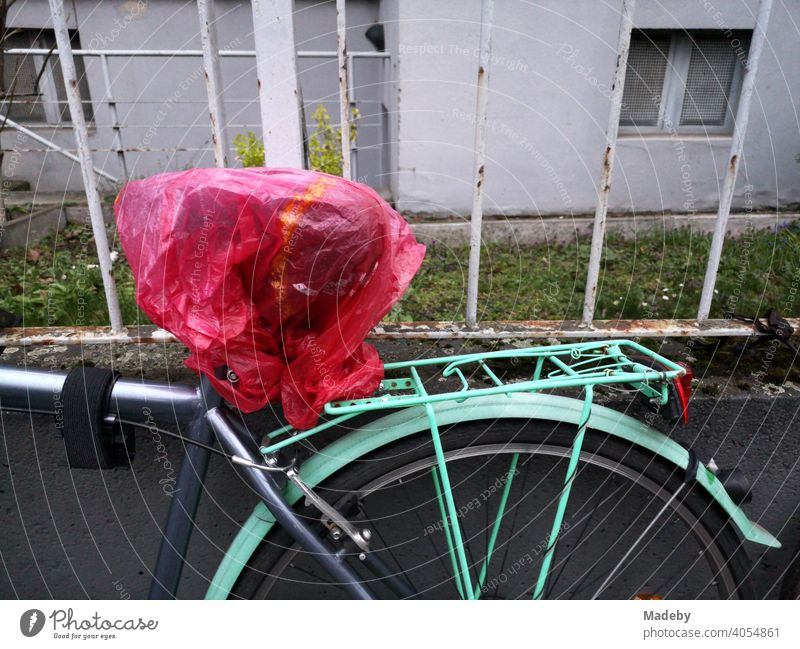 Bicycle in grey and turquoise with transparent red plastic bag over the saddle in front of an old iron fence in the north end of Frankfurt am Main in Hesse, Germany