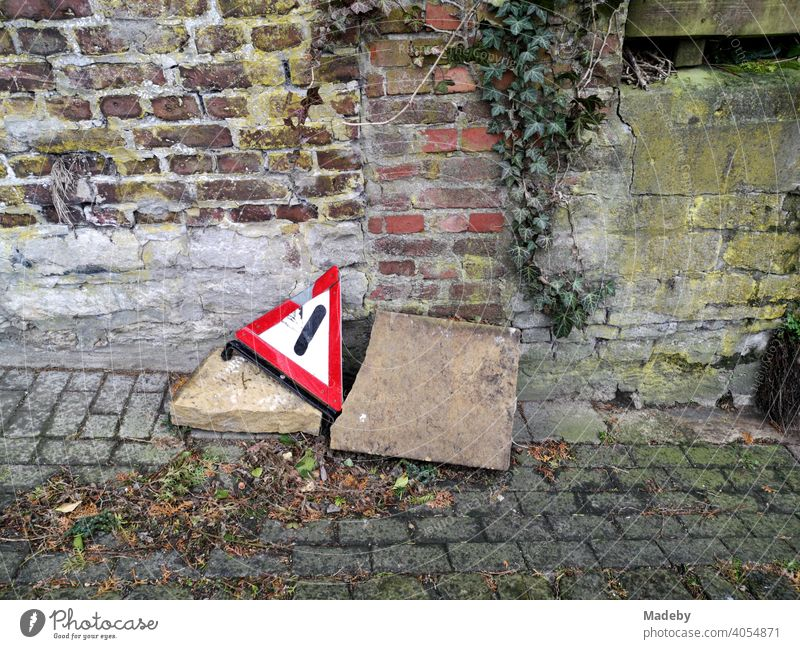 Broken warning triangle with big stones at the roadside on old cobblestones in front of brickwork in autumn in the old town of Oerlinghausen near Bielefeld in the Teutoburg Forest in East Westphalia-Lippe