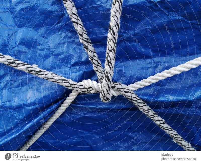 White and black and white ship's rope as a still life on a blue tarpaulin over a boat on a trailer in Oerlinghausen near Bielefeld in the Teutoburg Forest in East Westphalia-Lippe