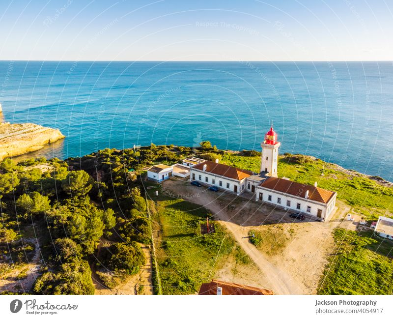 Cliffy coast with Alfazinha Lighthouse in Carvoeiro, Algarve, Portugal algarve lighthouse carvoeiro portugal portimao outdoor historic south copy scape red