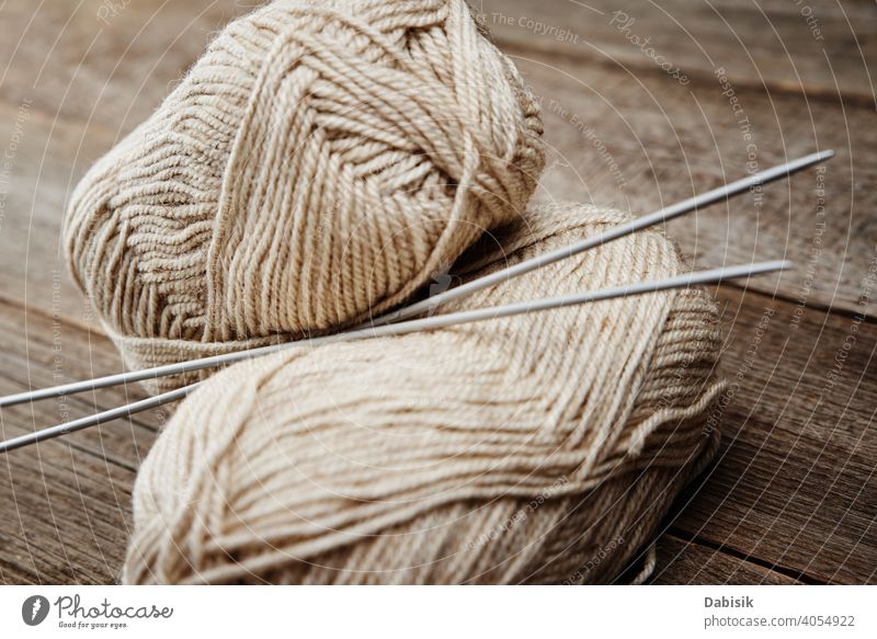 Two skeins of woolen yarn and needles for knitting on a wooden background needlework handmade hobby thread craft material warm soft fashion textile homemade