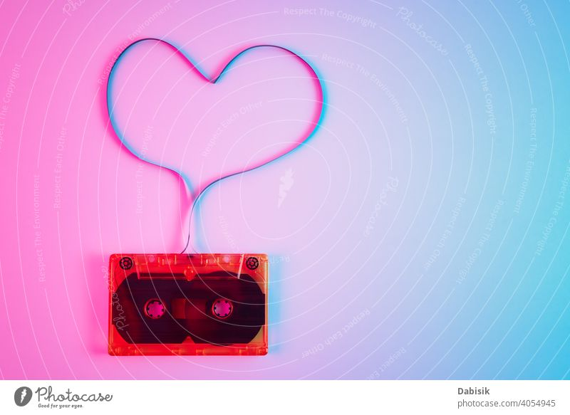 Retro cassette on colorful background with magnetic tape in shape of heart. Love music concept record old stereo vintage retro audio sound media style casette