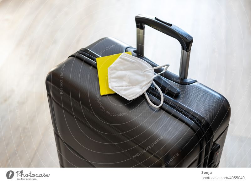 A case with a yellow vaccination certificate and a white FFP2 mask Suitcase voyage Vaccination certificate Yellow ffp2 mask covid-19 coronavirus Mask Protection