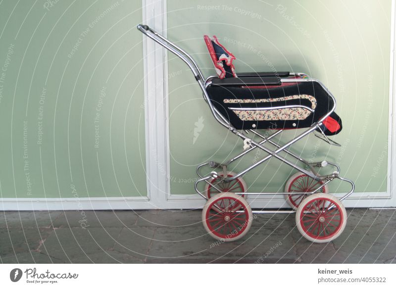 An old doll's pram recalls childhood in the seventies full of sadness and desolation doll car Baby carriage hallway Toys Infancy Day Parenting