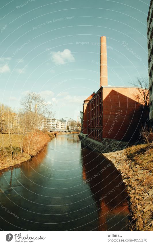 A sunny day by a quiet river with a factory with a smokestack on its banks. Time thinks the little clouds should also be mentioned. River Factory Chimney