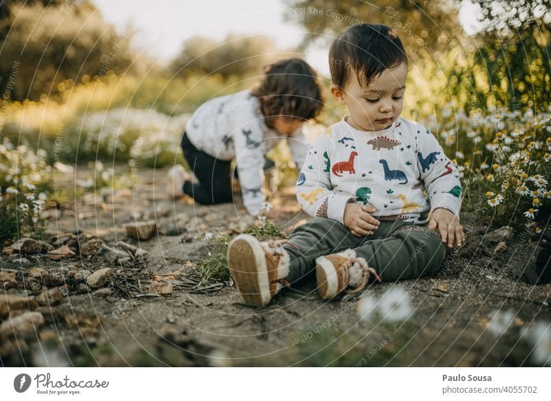 Brother and sister playing outdoors Spring Spring fever Spring flower Meadow Flower meadow Brothers and sisters Family & Relations Authentic Child childhood