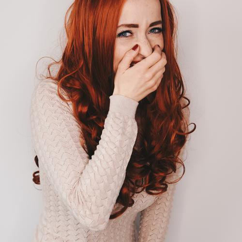 Woman with long red curly hair laughs looking at camera while holding a hand in front of her mouth Hair and hairstyles long hairs red hair Red Curly Nail polish