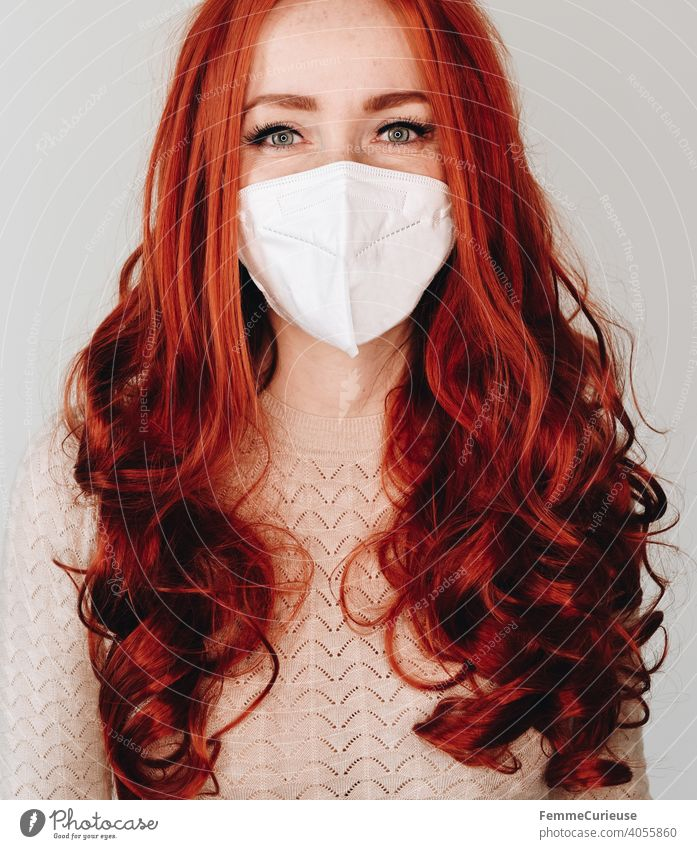 Woman with long red curly hair and FFP2 mask looking into camera with smiling eyes - portrait smilingly Smiling ffp2 Mask Face mask red hair long hairs