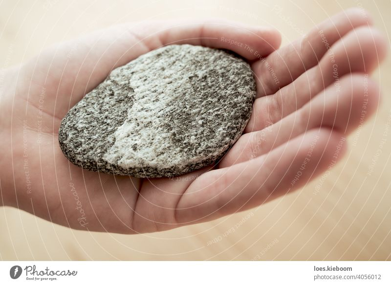 Woman holding stone with wave shapes as a symbol of balance for meditation hand harmony zen rock calm peace woman spa nature health relaxation natural spiritual