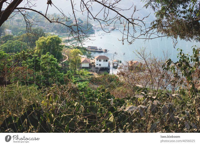 Top view on village coast along lake Atitlan through trees, San Juan la Laguna, Guatemala atitlan san juan aerial top guatemala beach local mountain water