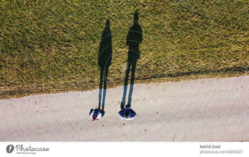 Aerial shot with a drone of two people with a long shadow Aerial photograph drone photo persons Man Woman Couple Street Meadow Field Shadow Sports off