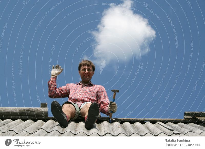 Cheerful man with hammer is sitting on roof of house, looking at camera and waving his hand against background of clean blue sky with one round cloud. Lower angle. Copy space for text.