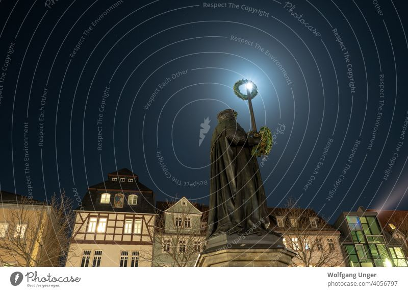 Longexposure in jena at night with full moon and Hanfried statue downtown holzmarkt architecture city street thuringia winter landmark lights