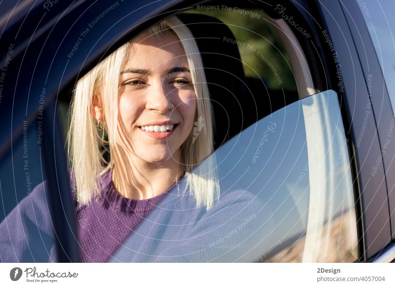 Young smiling woman steering car at sunset person hire hiring insurance owner safety successful test driver happiness joyful leasing looking pleasure purchase