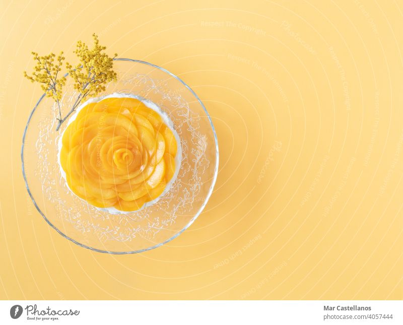 Three milks dessert decorated with peaches on yellow background. Copy space. Top view. creamy sweet fresh jelly fruits panna cotta recipe Colombia