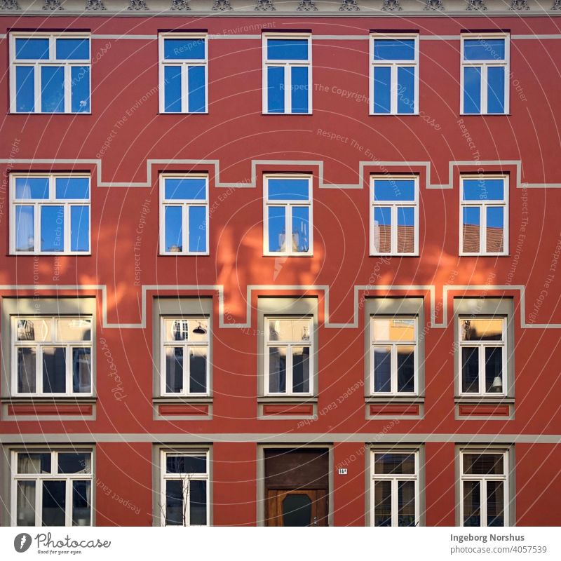Red house facade with patterns around the windows urban exterior glass geometric building architecture rows edifice design architectonic outdoors structure