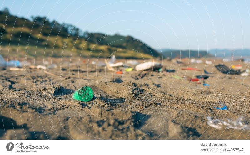 Dirty beach landscape full of waste trash garbage plastic sand dirty contaminated environment nature pollution coast plastic lid rubbish problem environmental