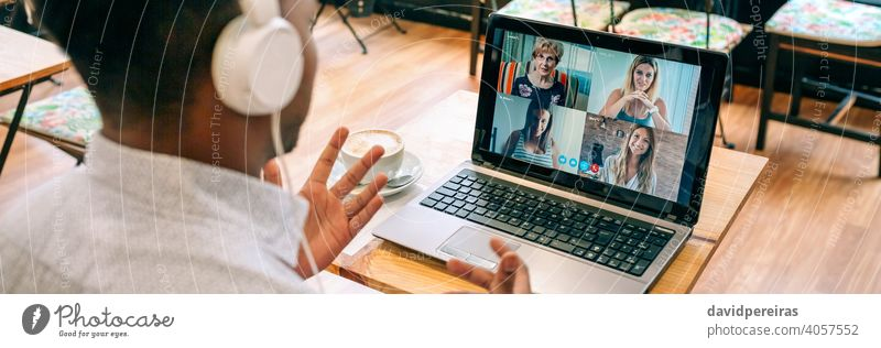 Man talking on video call with friends from a cafeteria unrecognizable man coffee shop internet laptop headphones banner web panoramic panorama online person