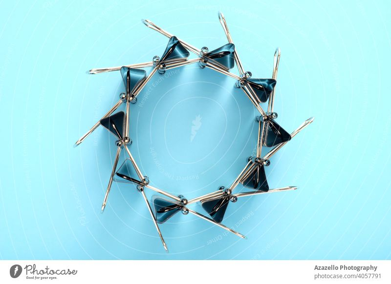A binder clips circle on blue background abstract art accessory black binder clip black paper clip business concept copy design documents dream education