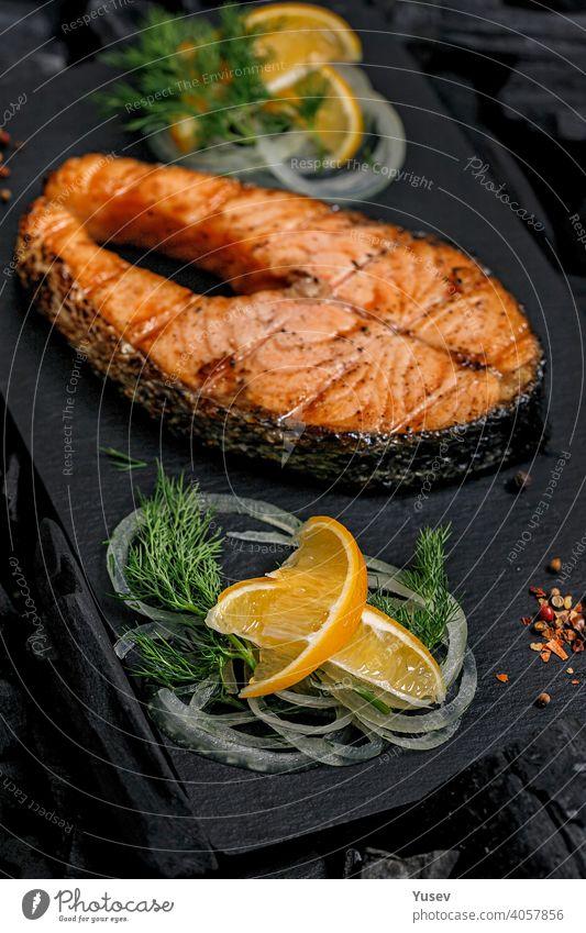 Vertical shot appetizing grilled salmon steak on a black ceramic board. Sea fish. Natural food. steaks background sea natural meal cooked dinner healthy fillet