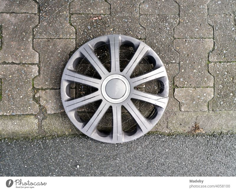 Lost silver hubcap on the interlocking pavement at the Senckenberganlage in the Westend of Frankfurt am Main in Hesse Wheel Wheel cover Wheel rim Star Rim