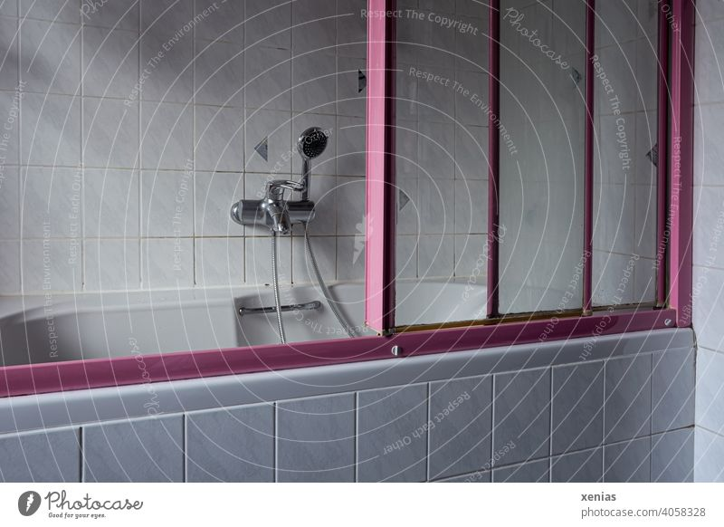 In the old bathroom is a senior inappropriate old bathtub with pink sliding doors, hand shower, handle and light tiles Bathtub Bathroom Hand shower bathe