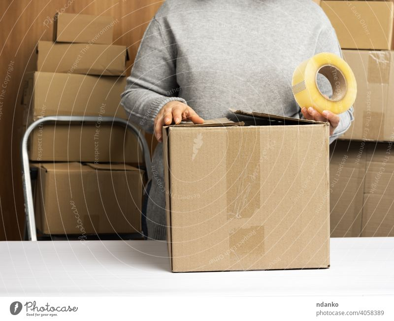 woman in a gray sweater holds a roll of duct tape and packs brown cardboard boxes on a white table, behind a stack of boxes lifestyle real adhesive tape many