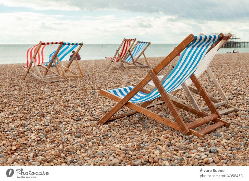 Empty red and blue striped deck chairs in Brigthon, UK. hammocks rental beach white sea material wood English Channel Atlantic Ocean Southern England