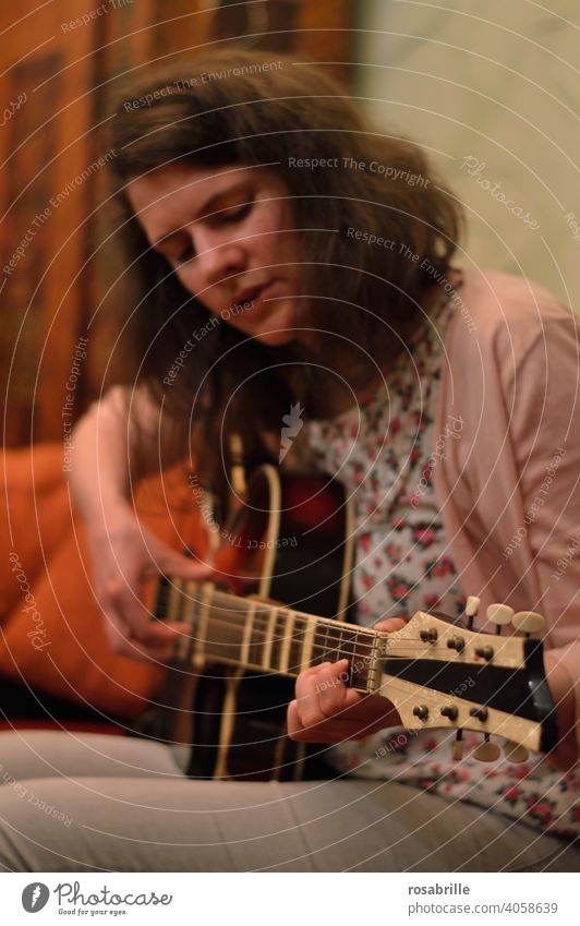 immersed in guitar playing - young brunette woman sits on sofa at home and plays guitar Music Guitar Woman Musician Playing Make music Art cabaret