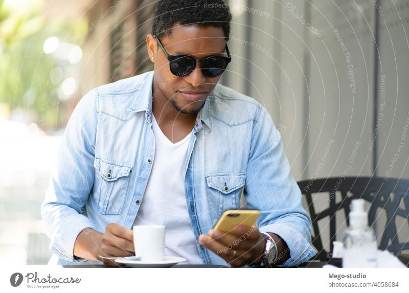 Man using his mobile phone at coffee shop. man urban city african american technology smartphone social media smile joy sunglasses enjoy device network wireless