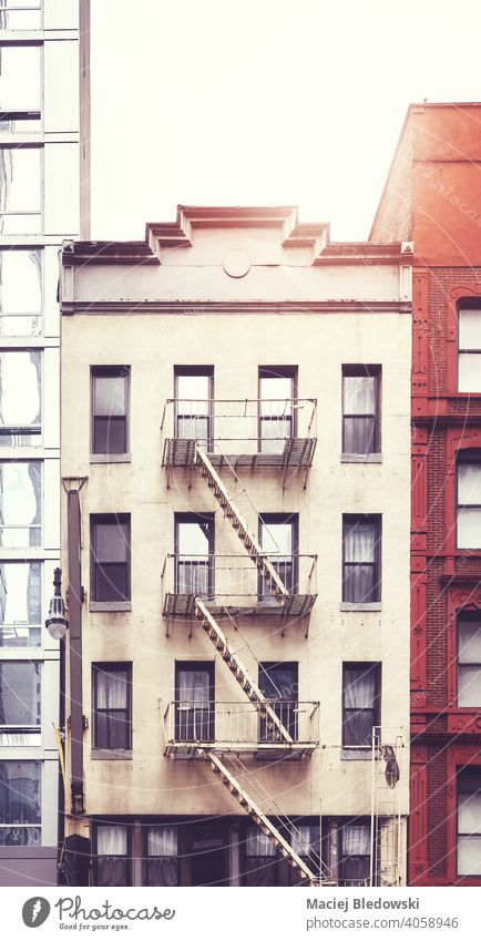 Tenement house with fire escape in Manhattan, color toning applied, New York City, USA. city building tenement vintage NYC retro symbol old residential home