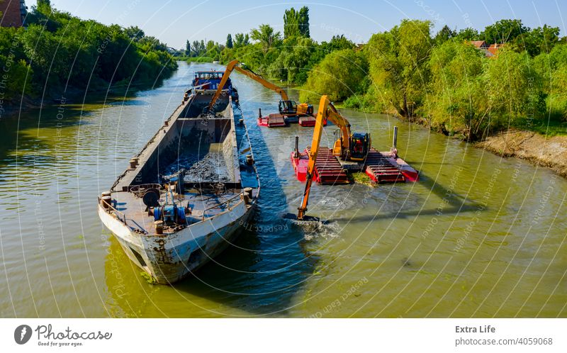 Aerial view of river, canal is being dredged by excavators Above Activity Backhoe Barge Boat Bucket Charge Civil Engineering Clean Dig Digger Dredge Dredger