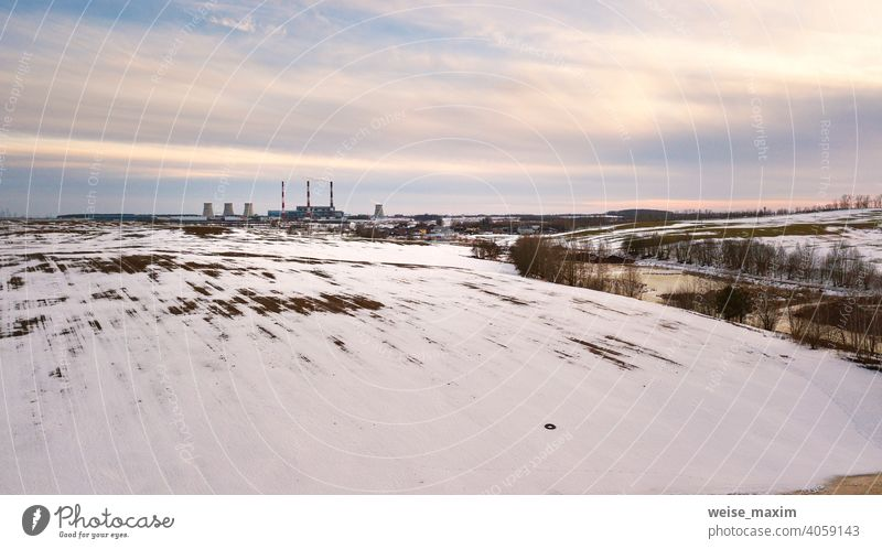 Aerial view of power station in evening light. Early spring urban industrial landscape. Snow melting, Season change industry factory environment plant pollution