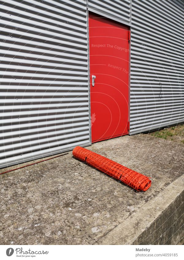 Red steel door in grey corrugated iron of a modern aircraft hangar with rolled-up barrier net in summer sunshine at the glider airfield Oerlinghausen near Bielefeld in the Teutoburg Forest in East Westphalia-Lippe