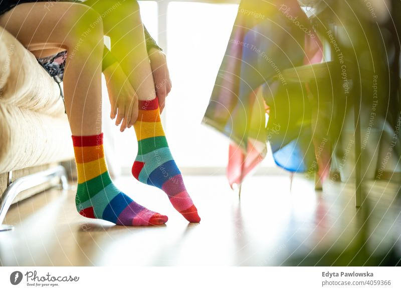 Close-up of a person putting on rainbow socks lgbtq rainbow flag real people pride legs non-binary gender fluid gender fluidity equality homosexual lesbian man
