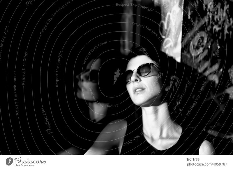The young woman enjoys the sun Young woman Brunette portrait Looking into the camera pretty Sunglasses 1 Beauty Photography Black & white photo naturally Town