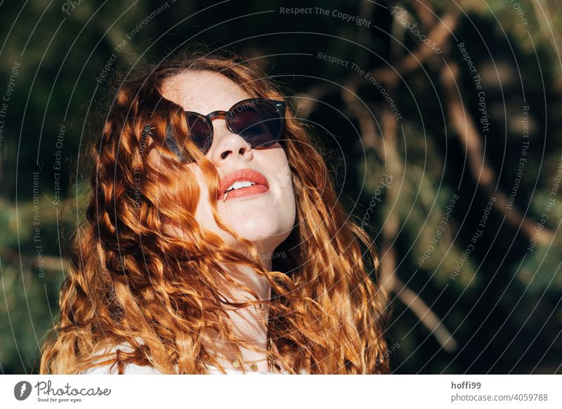 the young woman with sunglasses looks into the warm sun Spring Spring fever Joy Curl people Nature Sunglasses Spaaziergang vacation Elegant jand wife naturally