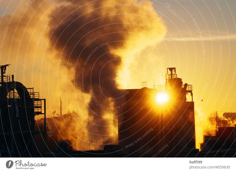 Sunrise, sunset with emissions from an industrial plant CO2 emission Fine particles Carbon dioxide Environmental pollution Steam Chemical Industry Chimney Roof