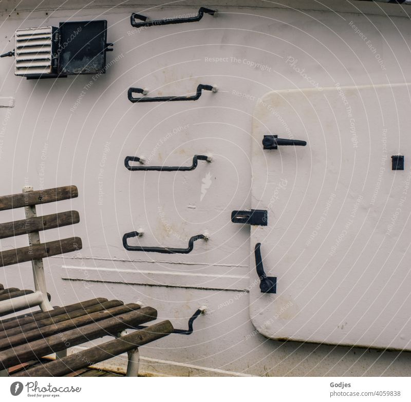 Seating in front of a metal ship's wall with steps and hatchway Navigation Watercraft bench door Hatch Stairs Ladder Exterior shot Day Colour photo Harbour Old