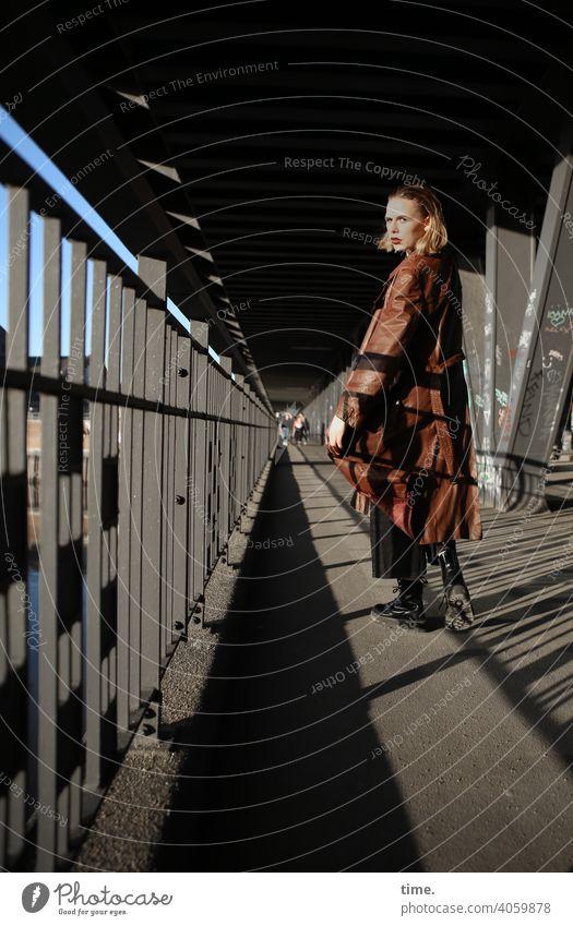 Lara Skeptical Mysterious urban Shadow sunny Bridge pier Metal leather coat Coat hair Blonde Looking Woman Going look around