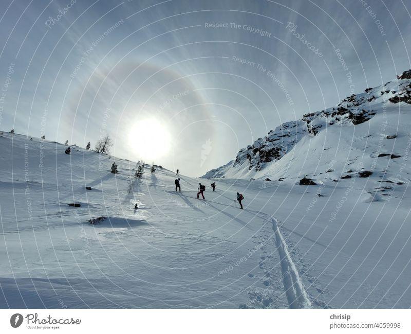 Ski tour towards the sun ascent track Snow track Winter Winter sports winter landscape Sports go on tour tourers Sunlight Ring Sky Nature naturally Light