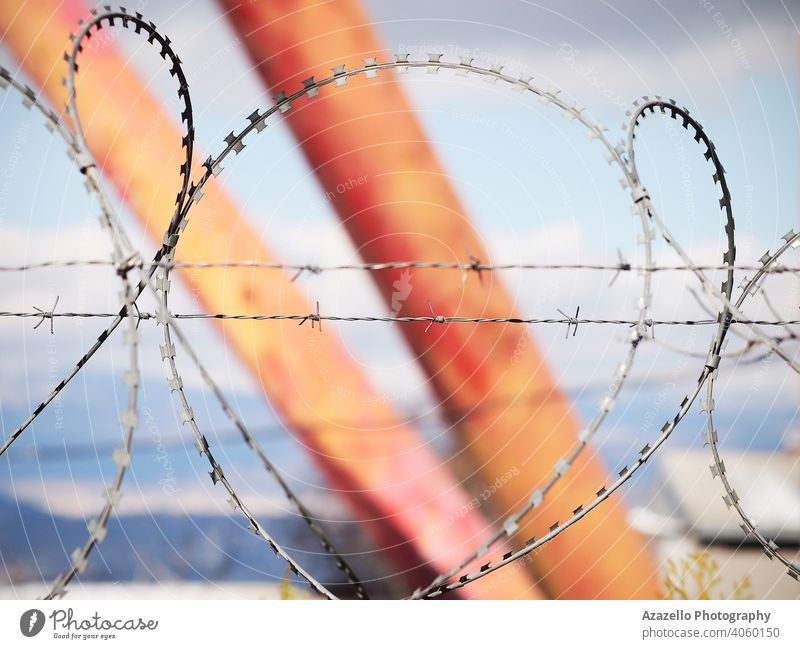 Barbed wire over the fence on a blurred background barbed barbed wire blue blurry bokeh background border boundary concept danger entrance freedom
