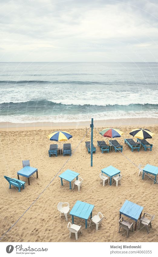 Aerial view of an empty tropical beach with umbrellas, sunbeds, tables and chairs, color toning applied, Sri Lanka. aerial resort vacation tourism season