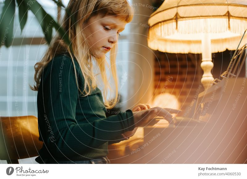 young girl playing keyboard at home activity aspiration beautiful caucasian child childhood daughter education family female hobbies instrument kid learn